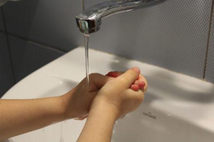 enfant qui laisse couler l'eau du robinet